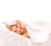 Cheerfull sexy blonde lying in bed. Stock Photos