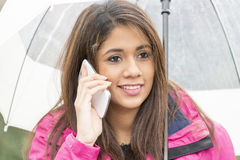 Cheerfull woman with umbrella talking by cellphone. Royalty Free Stock Image