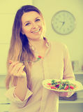 Cheerfull young woman eating tasty green salad. At home Royalty Free Stock Photo