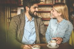 Cheerfully day. Couple at cafe. Happy young heterosexual couple at cafe having conversation and looking each other Royalty Free Stock Photo