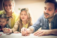 Cheerfully family at home. Family at home playing and drawing together. Focus on man stock image