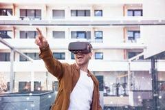 Cheerfully Jonge Volwassen Charmante Mens die Virtuele de Werkelijkheidsglazen gebruikt van VR Openlucht royalty-vrije stock afbeelding