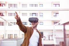 Cheerfully Jonge Volwassen Charmante Mens die Virtuele de Werkelijkheidsglazen gebruikt van VR Openlucht stock foto