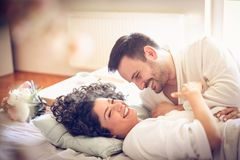 Cheerfully morning. Couple in bed. Young happy couple lying together in bed at morning . Valentines day Royalty Free Stock Photos
