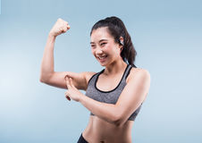 Cheerfully smiling asian sporty woman demonstrating biceps. Cheerfully smiling asian sporty woman demonstrating biceps on blue background Royalty Free Stock Images