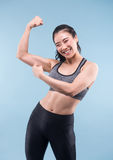 Cheerfully smiling asian sporty woman demonstrating biceps. Cheerfully smiling asian sporty woman demonstrating biceps on blue background Stock Image