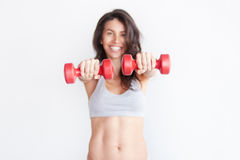 Cheerfully smiling sporty woman holding red dumbbells. Selective focus on hands. Shallow DOF. Cheerfully smiling sporty woman holding red dumbbells isolated on Royalty Free Stock Images