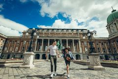 Cheerfully walking by the hand attractive couple in love along countryard at the Buda Castle Royal Palace in Budapest. Hungary stock photography