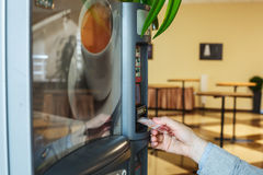 Cheerfulness at work - a mug of hot coffee. The coffee machine in the hall of the office. Man buys coffee royalty free stock photography