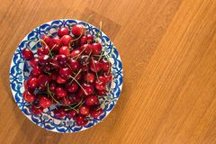 Cheery in the plate on the wooden table royalty free stock images