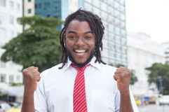 Cheering african american businessman with dreadlocks in the city Stock Image