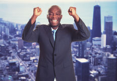 Cheering african american businessman with skyline. With skyline of city in background Stock Photography