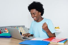 Cheering african american male student with laptop. At desk at home royalty free stock photo