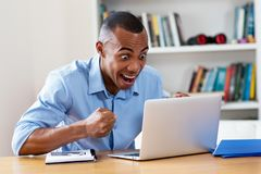 Cheering african american man at computer. At home at office stock image
