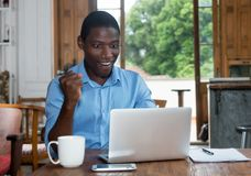Cheering african american man with laptop Royalty Free Stock Image