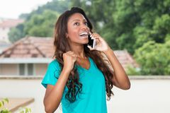 Cheering african american woman with long hair at mobile phone. Outdoors Royalty Free Stock Photo