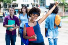 Cheering african american young adult woman with students in city. Cheering african american young adult women with students in city in summer royalty free stock photo