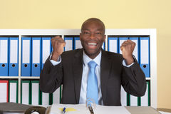 Cheering african businssman with blue tie at office Royalty Free Stock Images