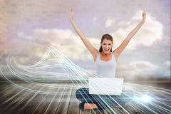 Cheering blonde using laptop with clouds Royalty Free Stock Photo