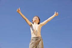 Cheering boy posing thumbs up. A cheering eight years old handsome boy posing with both thumbs up Stock Photo