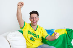 Cheering brazilian sports fan on sofa Royalty Free Stock Photo