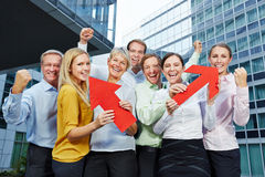 Cheering business people team winning. With red arrows pointing up stock image