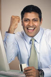 Cheering businessman with credit card stock photo