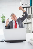 Cheering businessman at his desk Stock Photo