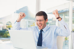 Cheering businessman at his desk Stock Images