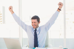 Cheering businessman at his desk Stock Photos