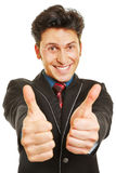 Cheering businessman holding both thumbs up. Cheering businessman holding both of his thumbs up Royalty Free Stock Photos