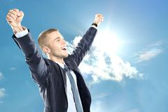 Cheering businessman winning something or having a successful business. Standing with arms raised and looking up on blue sky Royalty Free Stock Photography