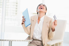 Cheering businesswoman shopping online with digital tablet. In her office stock photography