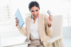 Cheering businesswoman shopping online with tablet pc Royalty Free Stock Image