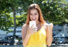 Cheering caucasian woman with red hair receiving good news on ph Stock Photography