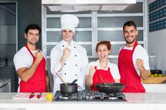 Cheering chef with team at kitchen. Of restaurant royalty free stock photography