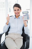 Cheering classy brown haired businesswoman showing her calculator. In bright office Royalty Free Stock Photography