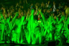 Cheering crowd. With hands up in green light. Motion blur stock photo