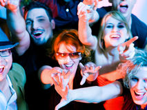 Cheering crowd in disco club. Crowd cheering - their rock idol or simply having fun in a club or disco party (attention - focus is on the stretched hands Stock Photo