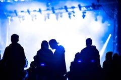 Cheering crowd in front of bright stage lights. Cheering crowd of people in front of bright stage lights. Music concert Stock Photography
