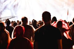 Cheering crowd in front of bright stage lights. Cheering crowd of people in front of bright stage lights. Music concert Royalty Free Stock Photo