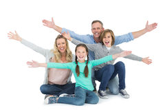 Cheering family with two children sitting on the floor royalty free stock photos