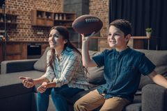 Cheering little boy and his mother sitting on couch with rugby ball while watching game