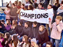 Cheering fans in stadium holding champion banner. Stock Photography