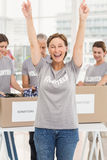 Cheering female volunteer in front of colleagues Royalty Free Stock Images