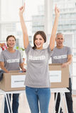 Cheering female volunteer in front of colleagues Royalty Free Stock Image