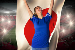 Cheering football fan in blue jersey holding japan flag Royalty Free Stock Images