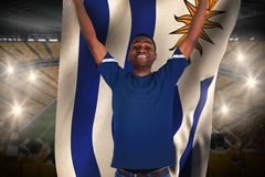 Cheering football fan in blue jersey holding urugauy flag Royalty Free Stock Photo