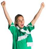Cheering football fan in green jersey Stock Photo
