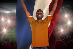 Cheering football fan in orange jersey holding netherlands flag Royalty Free Stock Photo